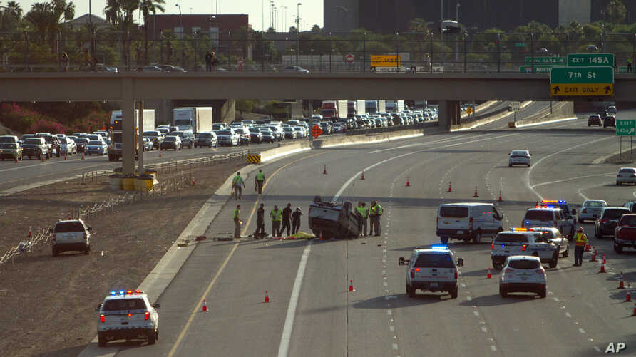 FILE - Traffic backs up on Interstate Highway 10 as authorities investigate the scene of a fatal accident in Phoenix, July 26, 2015. Road deaths rose 7.2 percent to 35,092 in 2015, the highest full-year increase since 1966.