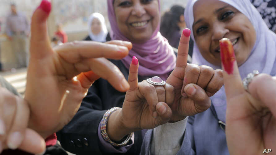 Egyptian women show their inked fingers after casting their votes at a polling station in Cairo. Egyptians are voting on a draft for their country's new constitution that represents a key milestone in a military-backed roadmap put in place after Pres