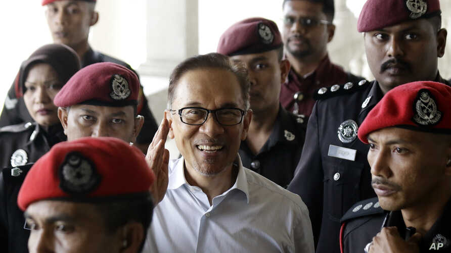 FILE - Deputy Prime Minister and opposition leader Anwar Ibrahim, center, smiles as he arrive at court house in Kuala Lumpur, Malaysia, June 13, 2017.
