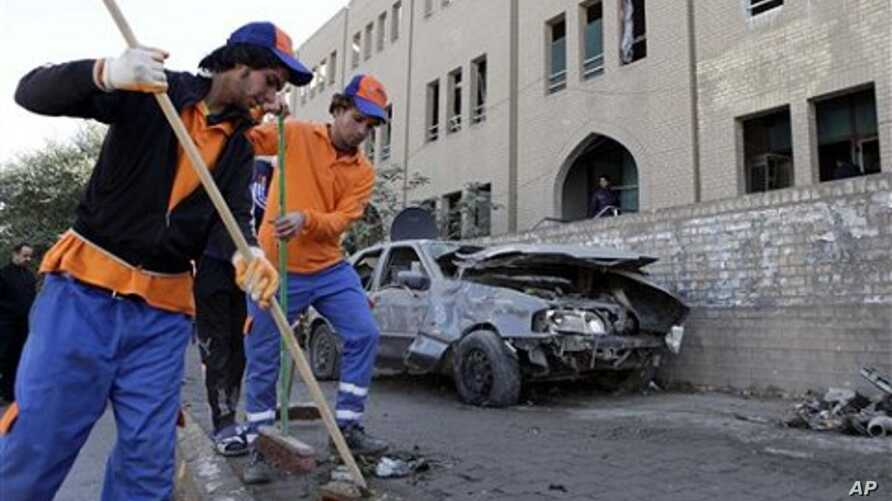 Workers sweep away debris after a bombing in Baghdad, Iraq, 23 Jan 2011.