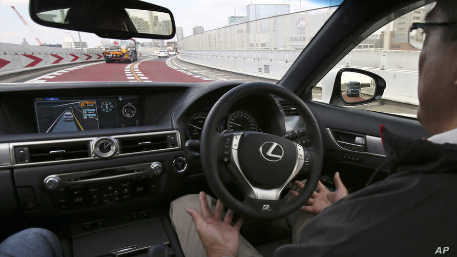 FILE - An employee of Toyota Motor Corp., drives automated driving test vehicle during a test drive of Toyota's self-driving technologies in Tokyo. Such cars are one field in which researchers are seeking to expand the limits of machine learning.