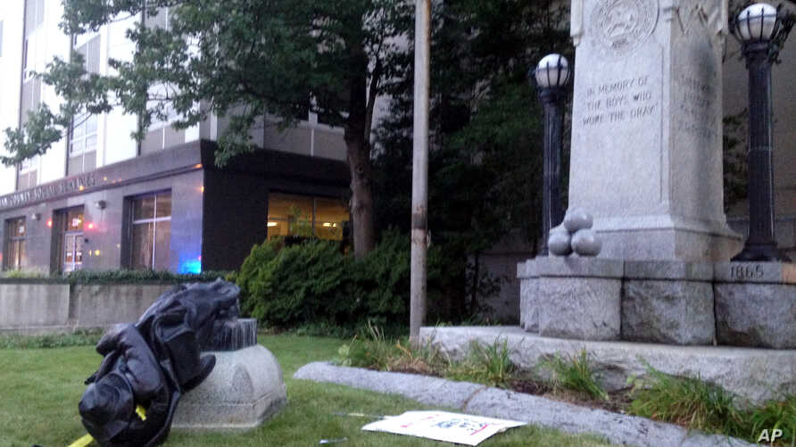 A toppled Confederate statue lies on the ground, Aug. 14, 2017, in Durham, N.C. Activists on Monday evening used a rope to pull down the monument outside a Durham courthouse. The Durham protest was in response to a white nationalist rally held in Cha...