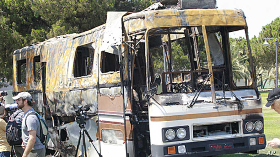 In this picture taken on a government-guided tour, a cameraman works near a destroyed private bus of Libyan leader Moammar Gadhafi at an area in the Bab al-Aziziyah compound in Tripoli, June 27, 2011.