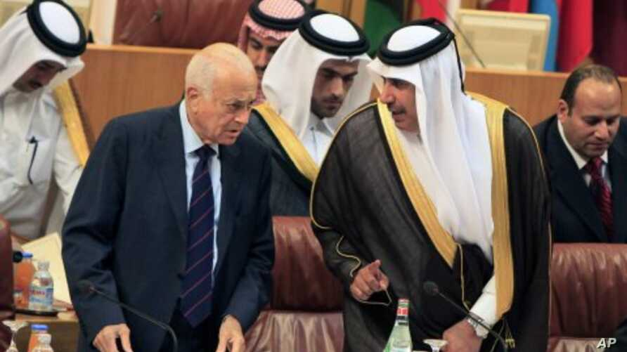 Arab League Secretary-General Nabil al-Arabi, left, talks to Qatari Foreign Minister Sheikh Hamad bin Jassim al- Thani, during an Arab foreign ministers meeting at the Arab League headquarters in Cairo to discuss the possibility of suspending Syria's