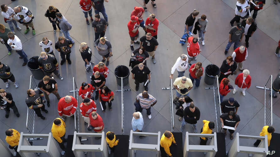 People wait to go through security at the T-Mobile arena before an NHL hockey game in Las Vegas, Nevada, Oct. 13, 2017. The city's tourism sector is bracing for changes in the aftermath of the massacre that killed 58 people at an outdoor music festiv