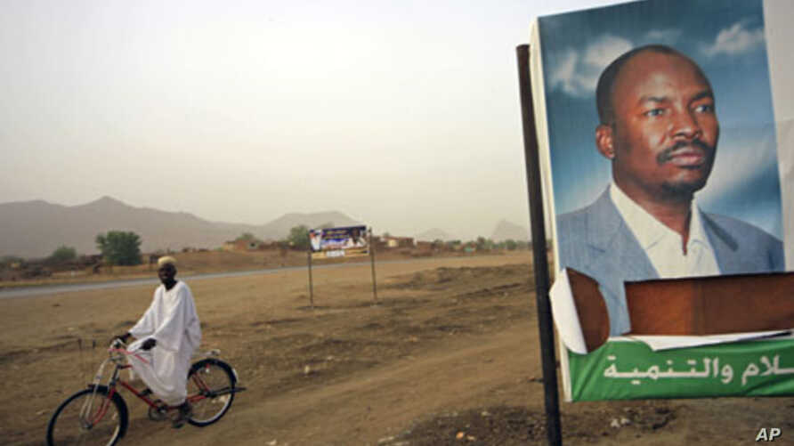 A man cycles past a gubernatorial election campaign billboard of NCP candidate for the governor's post Ahmed Haroun at Kadogli town, South Kordofan State, May 1, 2011