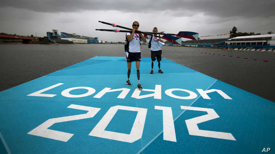 Rower Oksana Masters and her rowing partner Rob Jones from United States carry their oars after a training session ahead of the 2012 Paralympics Olympics in Eton Dorney, near Windsor, England, August 29, 2012.