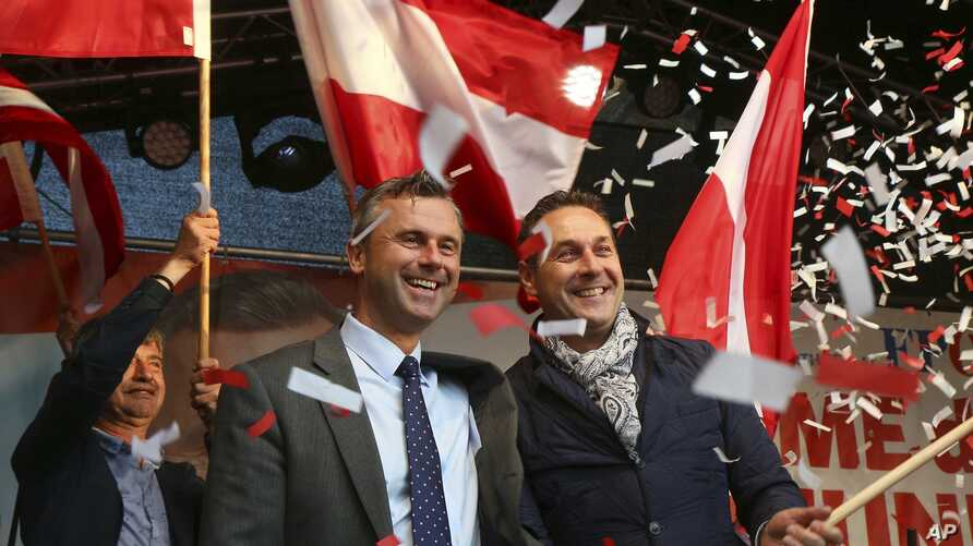FILE - In this May 20, 2016 file photo Norbert Hofer candidate for presidential elections of Austria's Freedom Party, FPOE, and Heinz-Christian Strache, from left, head of Austria's Freedom Party, FPOE, look out at supporters during the final electio