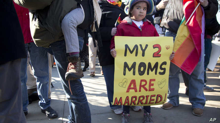 Gabriela Fore, 6, of Upper Darby Pa., holds a sign with her moms in front of the Supreme Court in Washington, Wednesday, Mar. 27, 2013, as the court heard arguments on the Defense of Marriage Act (DOMA).