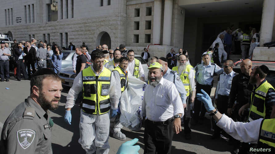 Israeli emergency personnel carry a covered body from the scene of an attack at a Jerusalem synagogue, Nov. 18, 2014.