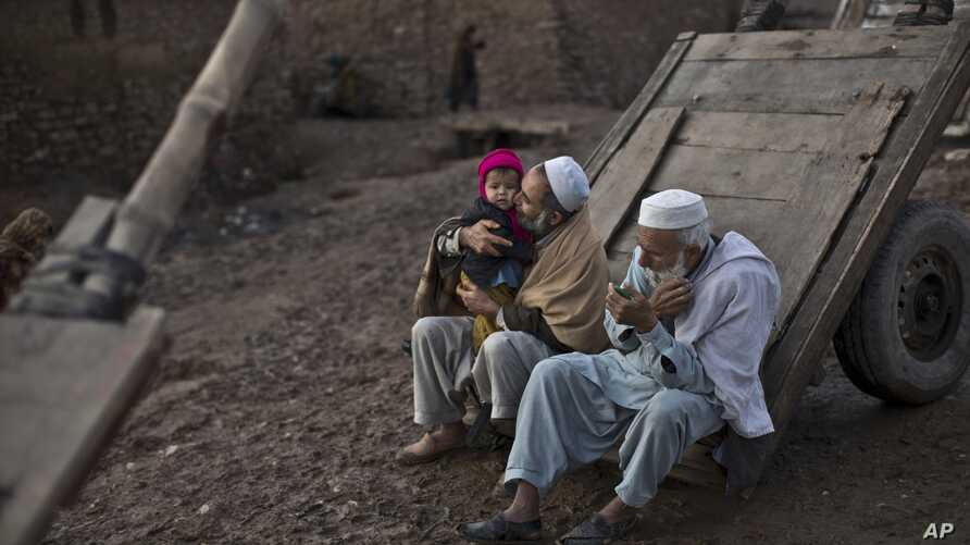 FILE - An elderly Afghan refugee trims his beard while another plays with his grandson on the outskirts of Islamabad, Pakistan, Feb. 19, 2015.