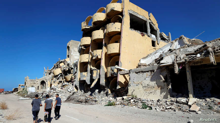 FILE - Youths walk past buildings that were destroyed during clashes between Libyan forces and Islamic State militants in Sirte, Libya, Nov. 1, 2017.