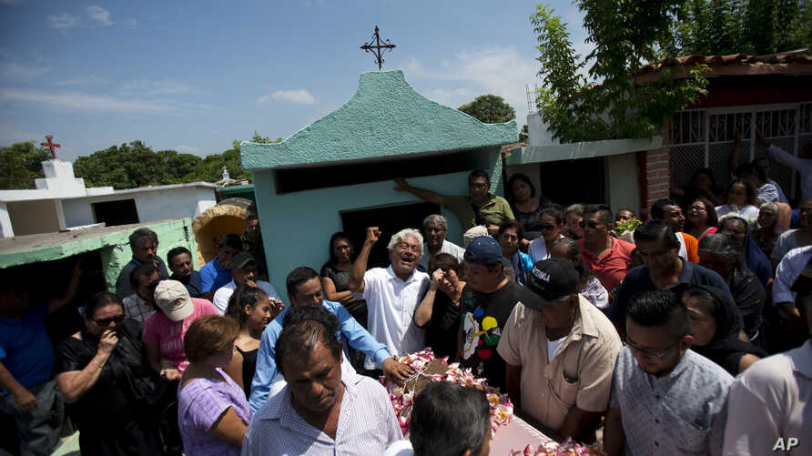 A family member laments the death of 64-year-old Reynalda Matus, as mourners prepare to bury her at the Miercoles Santo Cemetery in Juchitan, Oaxaca state, Mexico, Sept. 9, 2017. Matus was killed when the pharmacy where she worked nights collapsed du
