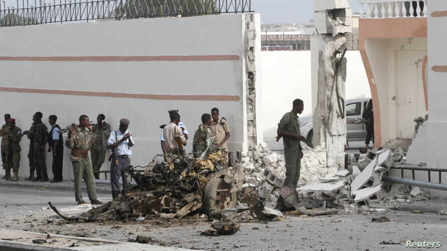 Somali government forces assess the scene of a suicide car explosion in front of the SYL hotel in the capital Mogadishu, Jan. 22, 2015.