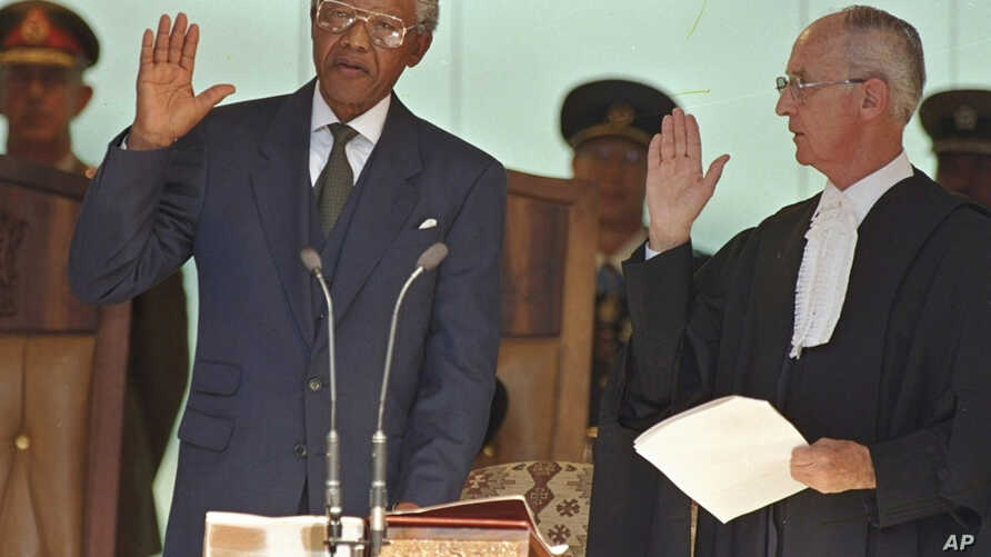 In this May 10, 1994, file photo, Nelson Mandela, left, takes the oath of office in Pretoria, South Africa, to become the country's first black President.