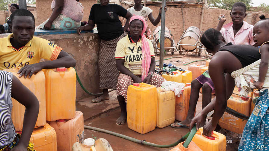 Women fill empty containers with water in the Nagrin neigborhood of Ouagadougou, Burkina Faso. Water trickles out of the faucet sometimes around 2 a.m., then by dawn the taps run empty at Dramane Drabo's laundry business on May 11, 2016.