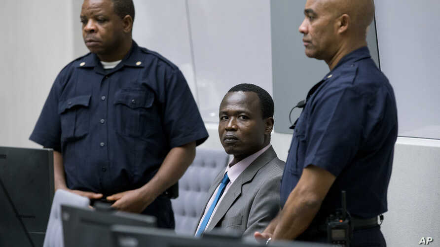 Dominic Ongwen, center, a senior commander in the Lord's Resistance Army, whose fugitive leader Kony is one of the world's most-wanted war crimes suspects, sits in the court room of the International Court in The Hague, Netherlands, Tuesday, Dec. 6, ...