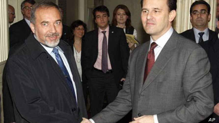 Israel's Foreign Minister Avigdor Lieberman, left, and his Greek counterpart Dimitris Droutsas shake hands in Athens, Greece, 12 Jan 2011