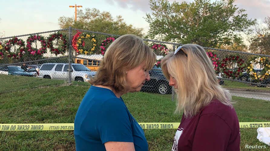 Beverly Turner and Michele Brown huddle to pray in front of a fence decorated with wreaths as students and faculty arrive at Marjory Stoneman Douglas High School for the first time since the mass shooting in Parkland, Florida, Feb. 28, 2018.