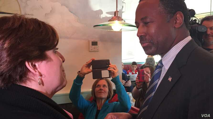 Presidential candidate Dr. Ben Carson talks with a woman at the Airport Diner in Manchester, New Hampshire, Feb. 7, 2016. (K. Gypson/VOA)