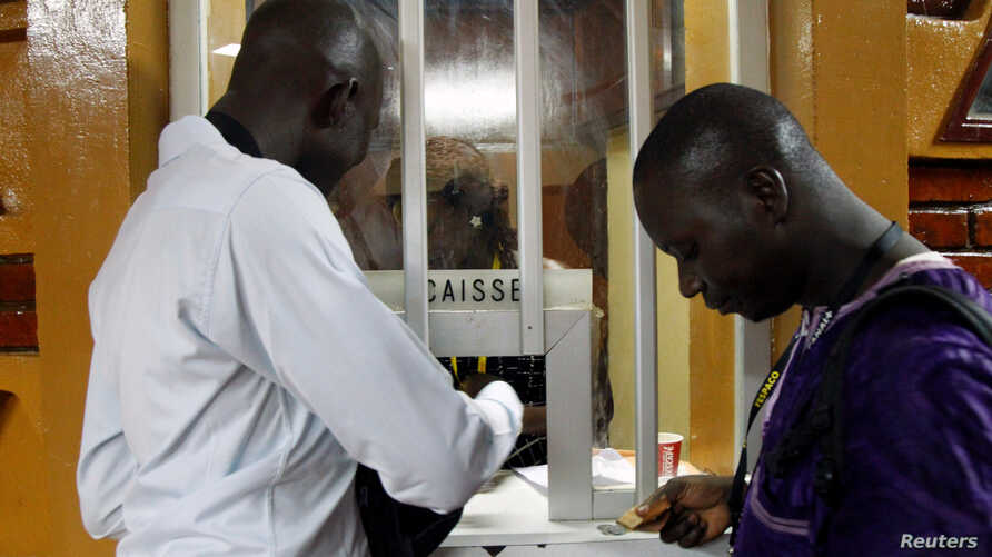 People buy cinema tickets at the entrance at cine Burkina during the Panafrican Film and Television Festival (FESPACO) in Ouagadougou, Burkina Faso, March 3, 2017.