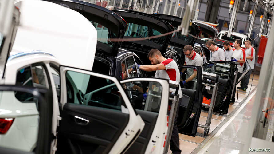 Workers assemble vehicles on the assembly line of the SEAT car factory in Martorell, near Barcelona, Spain, Oct. 31, 2018.