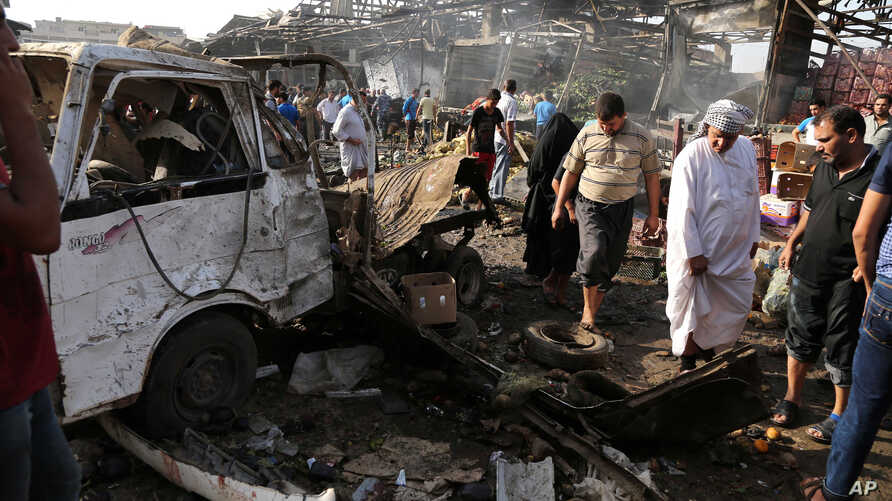 Civilians inspect the scene of bomb attack in Jameela market in the Iraqi capital's crowded Sadr City neighborhood Baghdad, Iraq, Thursday, Aug. 13, 2015.