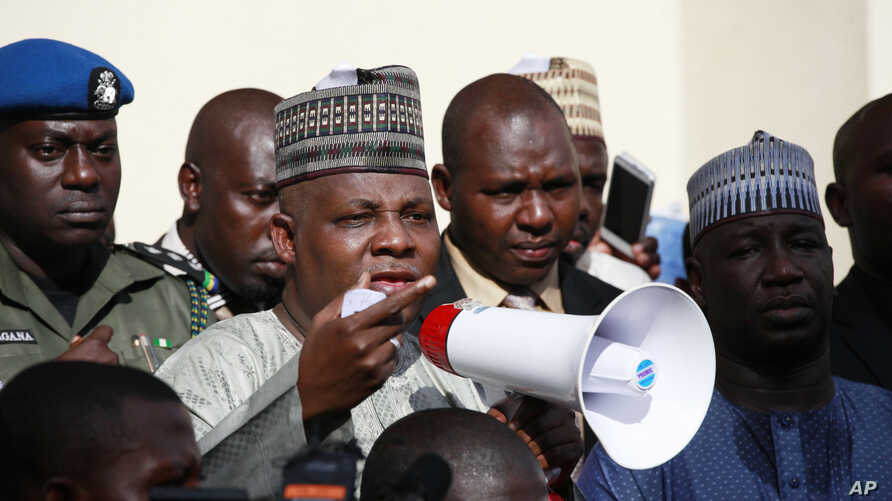 Borno state governor, Kashim Shettima, centre, addresses demonstrators who were calling on the government to rescue the kidnapped schoolgirls of the Chibok secondary school, in Abuja, Nigeria, May 13, 2014.
