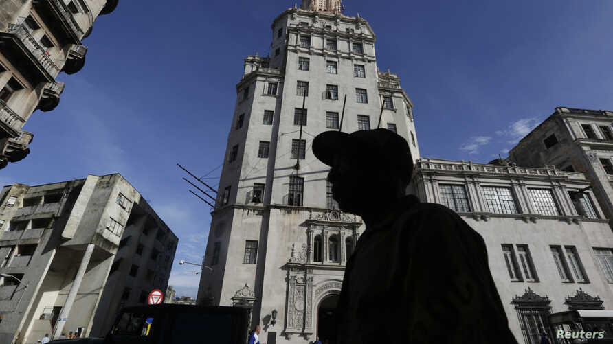 FILE - A man walks in front of the headquarters of Cuba's state-run telecommunications provider ETECSA in Havana, Oct. 24, 2014.