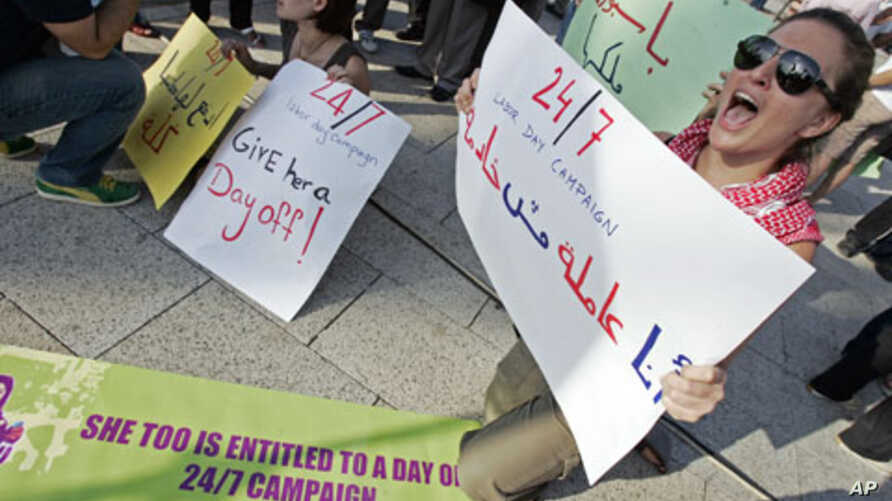 """Activists hold banners - one of which (R) reads, """"I am a worker, not a servant"""" - during a demonstration to support the rights of migrant domestic workers in Lebanon, in Beirut, Lebanon, May 1, 2010 (file photo)"""