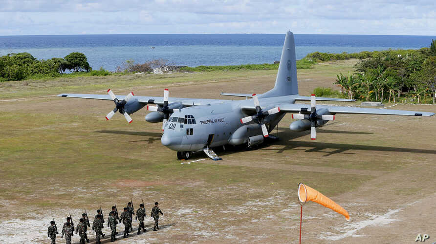 Philippine troops march as a Philippine Air Force C-130 transport plane carrying Philippine Defense Secretary Delfin Lorenzana, Armed Forces Chief Gen. Eduardo Ano and other officials, sits on the tarmac at the Philippine-claimed Thitu Island off the