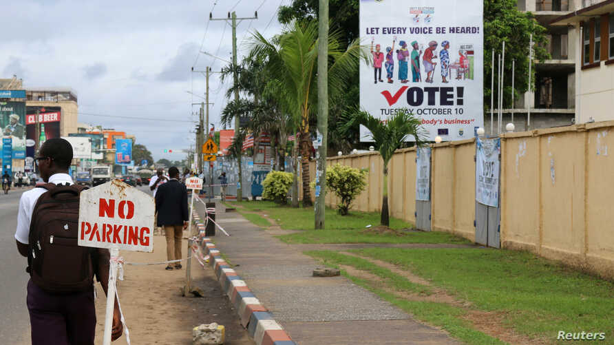 FILE - People walk past the headquarters of Liberia's National Elections Commission (NEC) in the Sinkor neighborhood of Monrovia, Liberia Nov. 6, 2017.