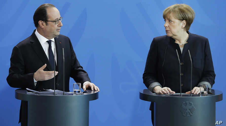 German Chancellor Angela Merkel, right, and the President of France, Francois Hollande, left, address the media during a joint statement as part of a meeting at the chancellery in Berlin, Germany, Jan. 27, 2017.