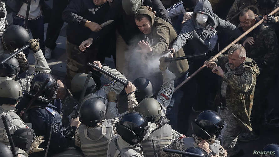 Radical protesters, including supporters of the All-Ukrainian Union Svoboda (Freedom) Party, clash with law enforcement members during a rally near the parliament building in Kyiv, October 14, 2014.