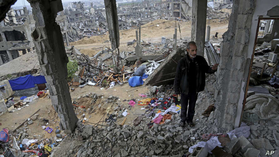 A Palestinian man stands in rubble of his house which was destroyed during the conflict between Israel and Hamas, in Gaza City's Shijaiyah neighborhood, Nov. 24, 2014.