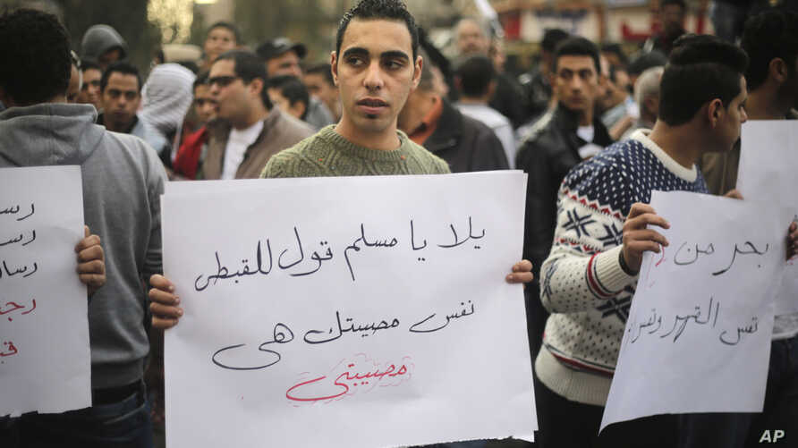 """An Egyptian man holds a poster with Arabic that reads """"Muslims and Copts are in the same tragedy"""" during a protest against the slaying of Egyptian Coptic Christians in Libya by militants associated with the Islamic State group, in Cairo, Egypt, Feb."""