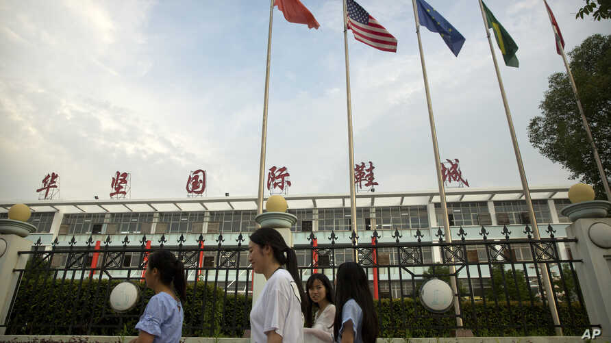 In this June 6, 2017, photo, Chinese, American, and other international flags fly as women walk past a Huajian Group shoe factory, the one time shoe maker for the Ivanka Trump brand, in Ganzhou in southern China's Jiangxi Province.