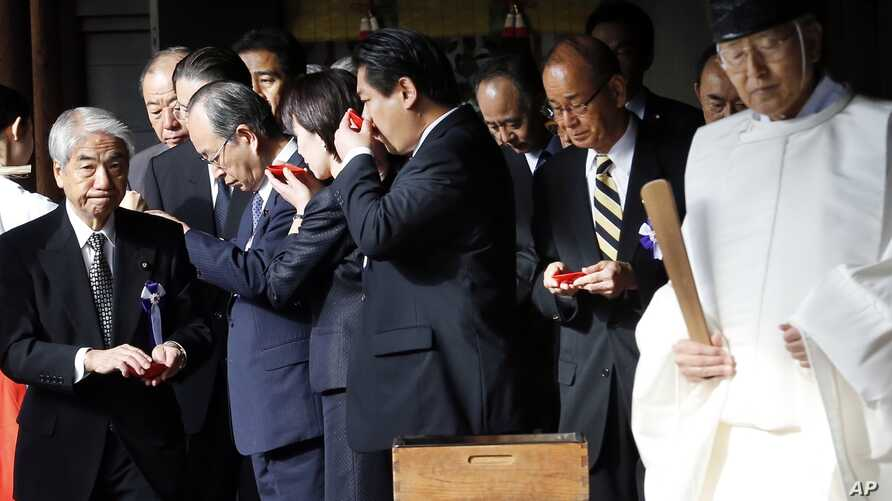 Group of Japanese lawmakers sip sake as they observe a Shinto ritual, Yasukuni Shrine, Tokyo, Oct. 18, 2013.