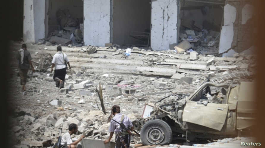 Soldiers are pictured through a window as they inspect the scene of a car bomb attack at a military police building in Mukallah city of the southern Yemeni province of Hadhramout. May 11, 2014.