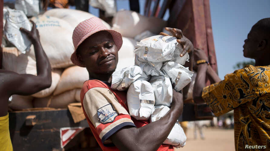 FILE - A man carries packages of food aid delivered by the U.N. Office for the Coordination of Humanitarian Affairs and World Food Program in Makunzi Wali, Central African Republic, April 27, 2017.