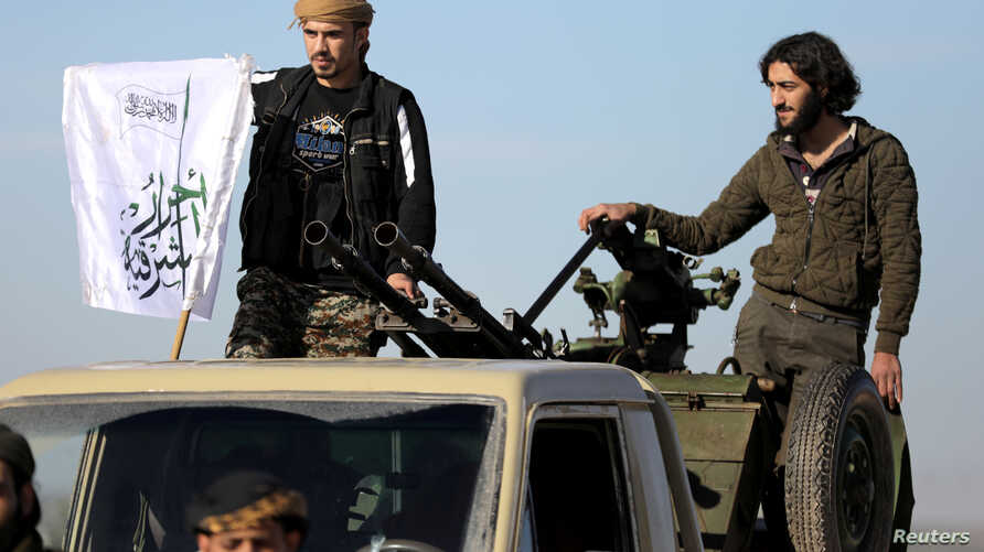 FILE - Turkish-backed Syrian rebels stand on the back of a truck at Manbij countryside, Syria, Dec. 29, 2018.