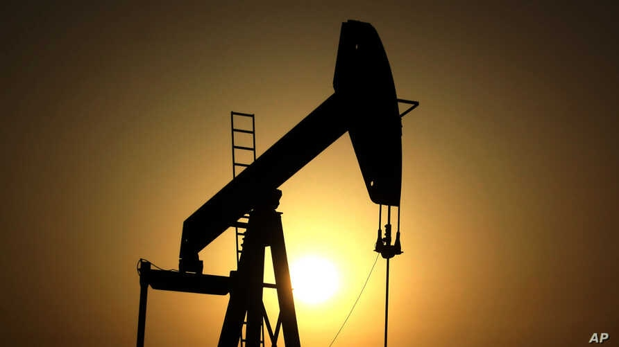 FILE - The sun sets behind an oil pump in the desert oil fields of Sakhir, Bahrain, June 8, 2011. OPEC nations have agreed in theory on the need to reduce their production to help boost global oil prices during a meeting last month in Algeria, but di