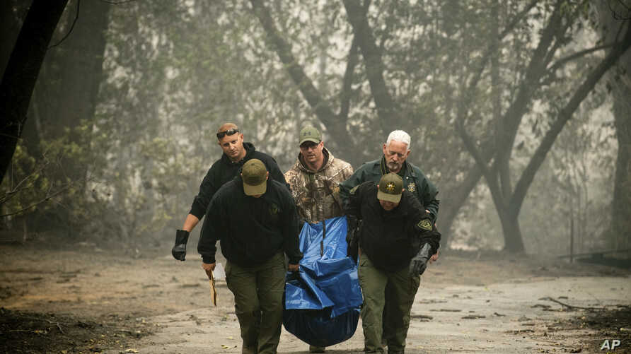 Sheriff's deputies recover the remains of a victim of the Camp Fire, Nov. 10, 2018, in Paradise, California.