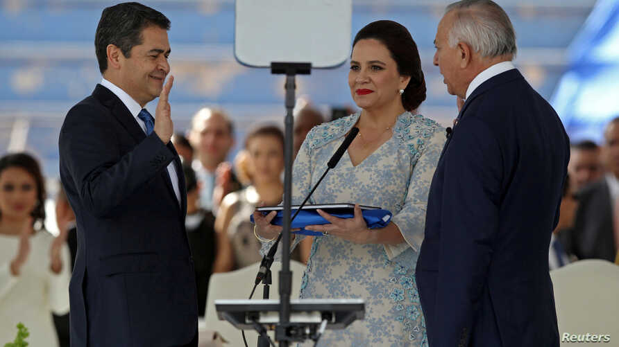 Honduran President Juan Orlando Hernandez, accompanied by his wife, Ana Garcia de Hernandez, and President of the National Congress of Honduras Mauricio Oliva, is sworn in for a new term at the Tiburcio Carias Andino National Stadium in Tegucigalpa,