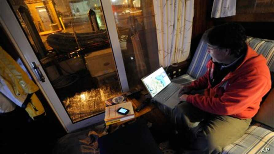 David C. Bond of Wickford, R.I. checks weather forecasts on his computer while riding out Sandy on his boat docked in Annapolis, Md. Monday, Oct. 29, 2012. Sandy continued on its path Monday, as the storm forced the shutdown of mass transit, schools