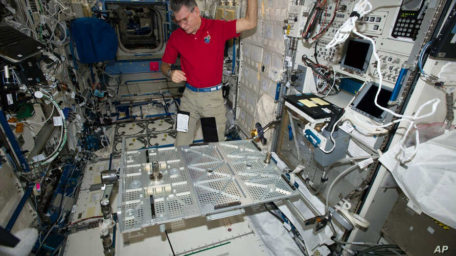 In this photo provided the European Space Agency on Wednesday, Oct. 25, 2017, Italian astronaut Paolo Nespoli looks at the Multipurpose Transporting Plate aboard the International Space Station. Pope Francis is making his first phone call off the pla