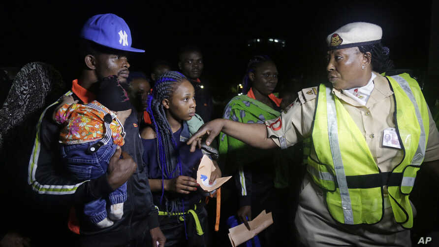 FILE - An unidentified Immigration officer, right, speaks to Nigerian returnees from Libya upon arrival at the Murtala Muhammed International Airport in Lagos Nigeria, Dec. 5, 2017.