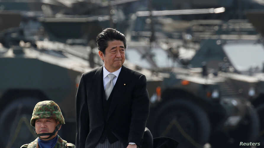 FILE - Japanese Prime Minister Shinzo Abe reviews Japanese Self-Defense Forces' (SDF) troops during the annual SDF ceremony at Asaka Base, Japan, Oct. 23, 2016.
