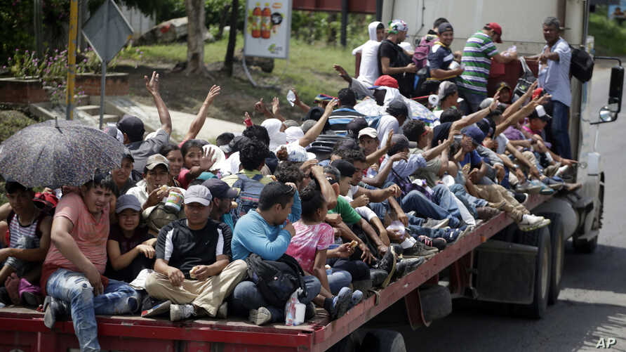 Honduran migrants who are traveling to the United States as a group, get a free ride in the back of a trailer truck flatbed, as they make their way through Teculutan, Guatemala, Oct. 17, 2018.