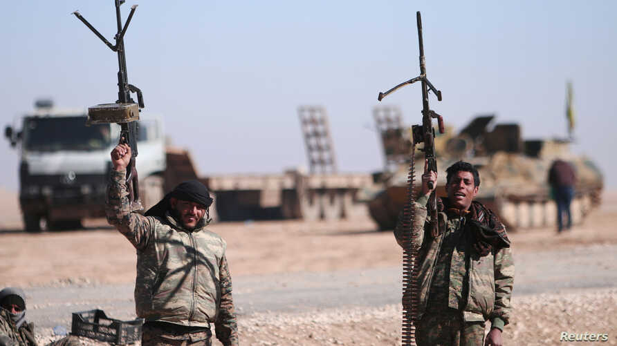 FILE - Syrian Democratic Forces (SDF) fighters hold up their weapons in the north of Raqqa city, Syria.